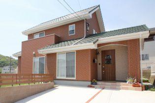 緑の屋根とレンガ調の外壁が印象的な外観です。